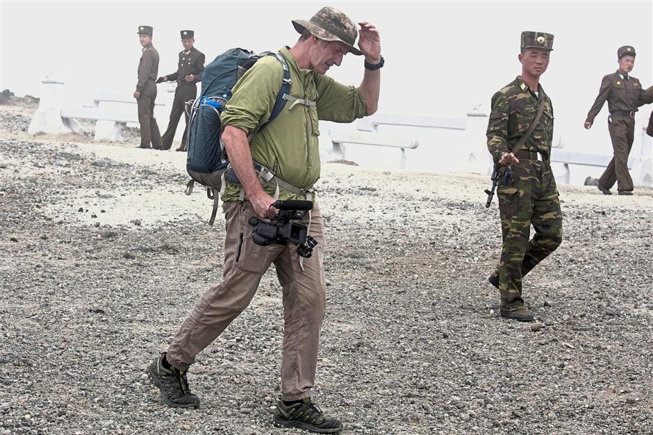 Spirit of adventure: Shepherd walking past North Korean soldiers while leading an off-road hike on Mount Paektu. — AP