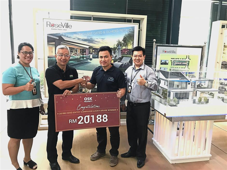(Top) One of the winners of OSK Property's 20188 Ways to Save  package receiving the prize from the company management. (Right pic)  An aerial view of the 30-acre recreational park which has walking and cycling trails.
