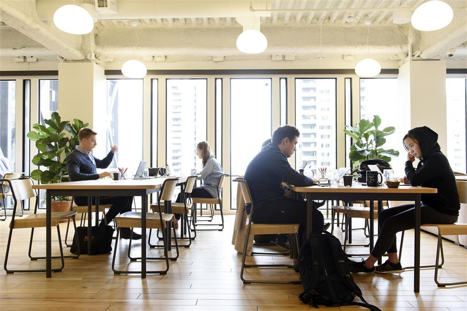 Members work on laptop computers in a common room at the Embarcadero WeWork Cos Inc. offices in San Francisco, California, U.S., on Thursday, Oct. 19, 2017. WeWork has focused its attention on Asia since 2016 with the opening of its first facility in Shanghai amid booming demand for flexible work spaces. Photographer: Michael Short/Bloomberg