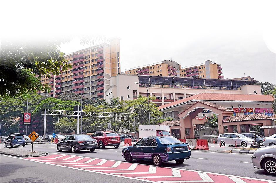 Guarding the area: The century-old Tsun Jin High School and the iconic Loke Yew flats at the back.