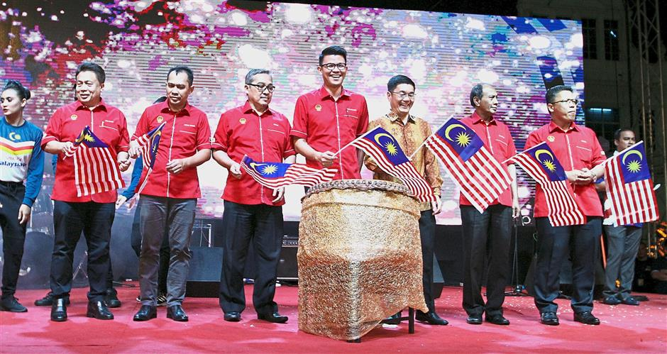 Tan (fourth from right) flying the Jalur Gemilang with other dignitaries during the launch of the celebration.