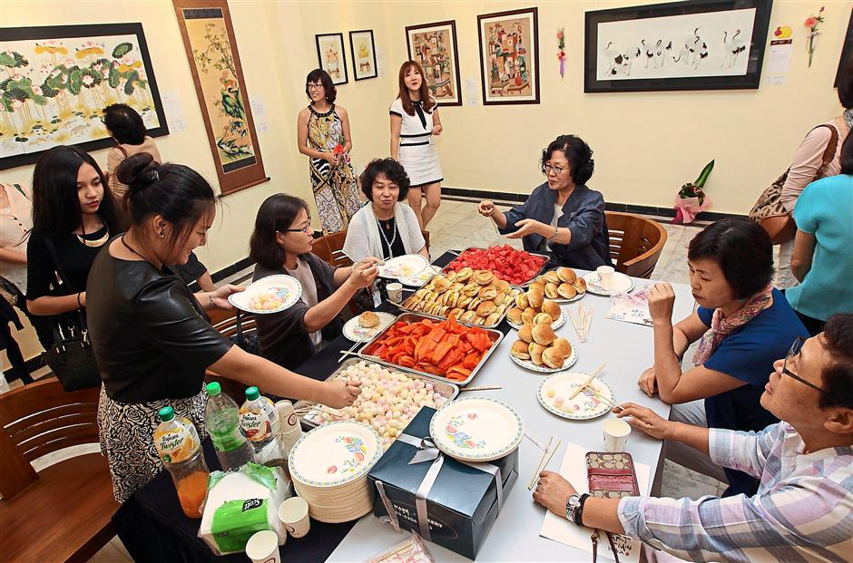 For sustenance: Visitors and members of Art of Minhwa Association indulge in Korean delicacies after touring the exhibition at the MaTiC Art Gallery