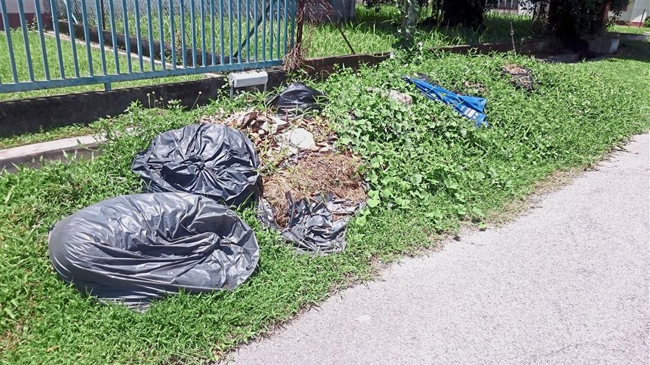 Bags of garden refuse left uncollected for so long that they have become hidden by overgrown grass along Selasar Chateau in Chateau Garden, Ipoh.
