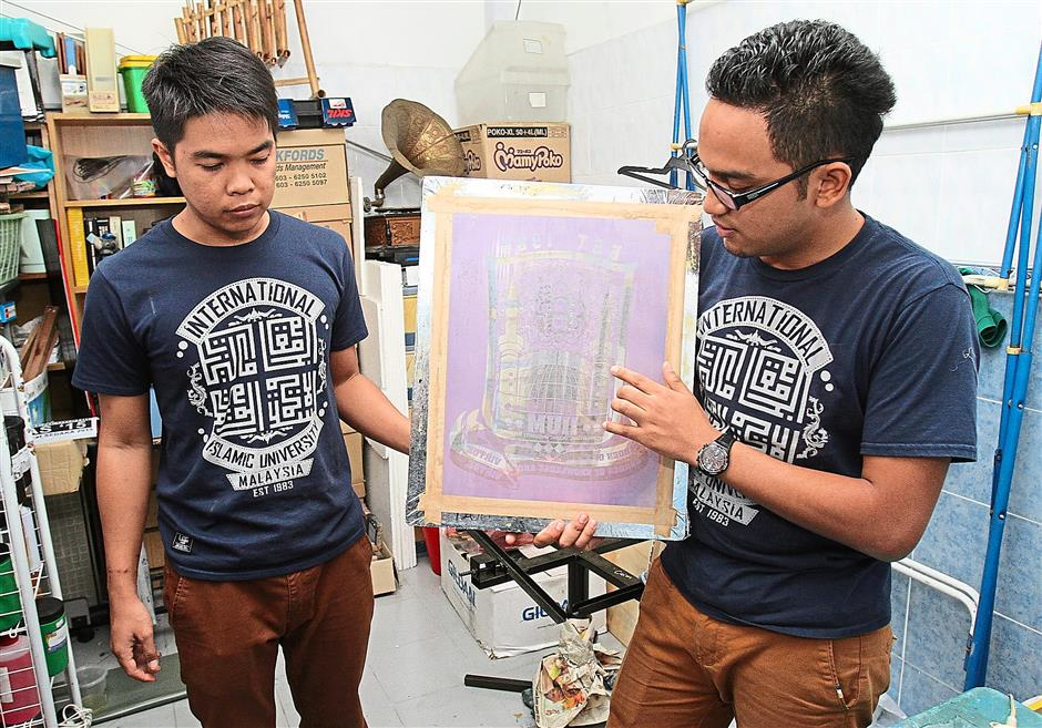 Template: Asyraf (right) showing how they use a casting mould to make their prints.