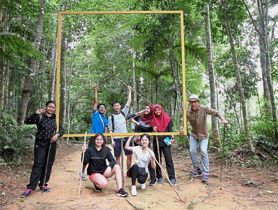 The group, with Chan (right), pose by the National Geographic-esque yellow rectangle frame at the Awana Bio Park.