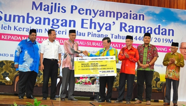 Chow (fourth right) handing over the mock cheque amounting to RM240,000 to Zulkifli during the presentation ceremony at the SP Arena in Seberang Jaya.