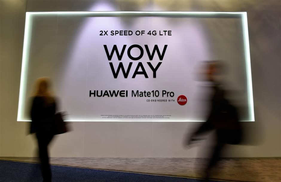 LAS VEGAS, NV - JANUARY 10: Attendees walk by an advertisement for the Huawei Mate 10 Pro smartphone at the Huawei booth during CES 2018 at the Las Vegas Convention Center on January 10, 2018 in Las Vegas, Nevada. CES, the world\'s largest annual consumer technology trade show, runs through January 12 and features about 3,900 exhibitors showing off their latest products and services to more than 170,000 attendees.   David Becker/Getty Images/AFP == FOR NEWSPAPERS, INTERNET, TELCOS & TELEVISION USE ONLY ==