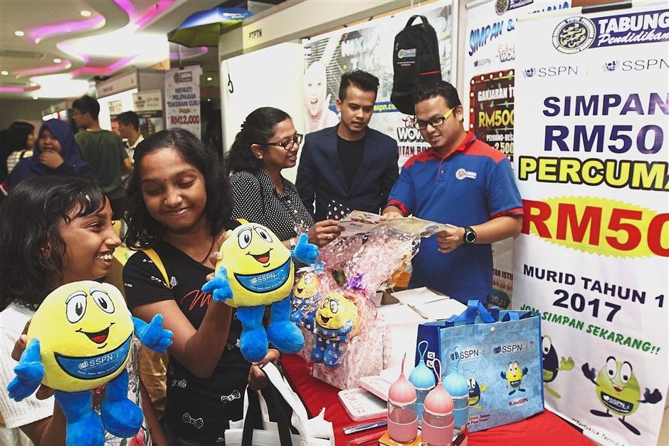 Young visitors admiring the free gifts which will be given out to those who sign up for a savings scheme at the PTPTN booth during the event.
