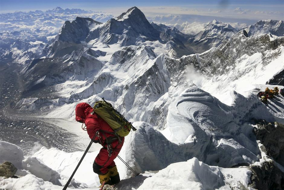 One small step for man, one giant step for mankind: A climber tackling the Hillary Step on the way down from Mount Everest.