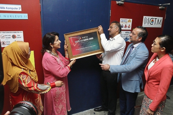 (From second left) Gurmit and Ramkarpal hanging a signed frame on the wall outside the Karpal Singh Digital Hub in SK Sungai Gelugor in Penang. Looking on from left are headmistress Fairus, Jagdeep and Syerleena.