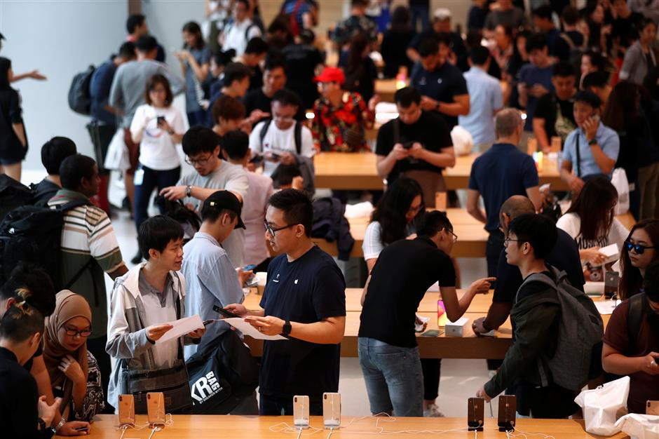 Customers look at the newly launched iPhone XS and iPhone XS Max at the Apple Store in Singapore September 21, 2018. REUTERS/Edgar Su