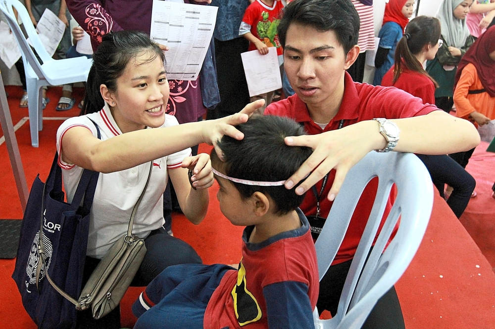 Dr Heng Kai Voon (left) and medical undergraduate Danial Haziq taking the measurements of a child in PPR Lembah Subang.