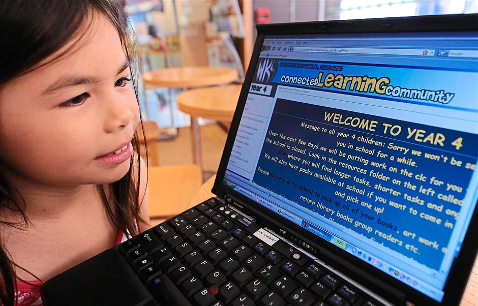 A primary student looks at a school website where online learning is set up as schools close because of the outbreak of swine flu  in Hong Kong on June 19, 2009.  The closure of dozens of Hong Kong schools to try to halt the spread of swine flu has kept thousands of children at home, but new technology has meant they can no longer escape their teachers.      AFP PHOTO/MIKE CLARKE