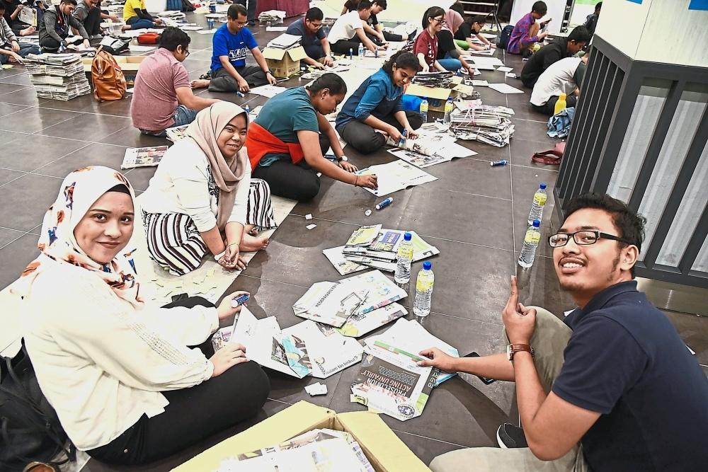 Volunteers turning used newspapers into paper bags.