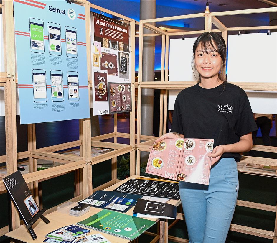 Creative Media Design student Lim Pei Yee showing off the promotional materials she came up with for a cafe in Taiping, as well as a mock app for easy bus travels. (Jeremy Tan / Aug 28, 2018)