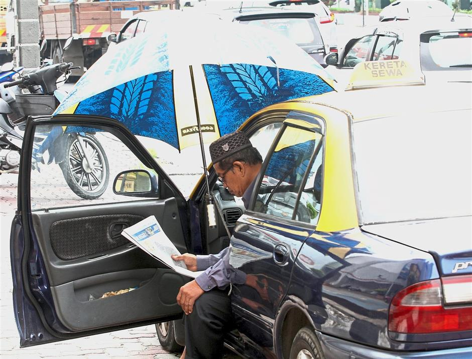 A taxi driver takes shelter inside his vehicle under an umbrella as there is no permanent base for drivers to rest.