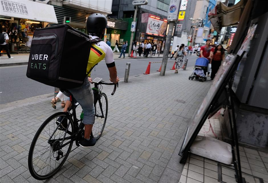This picture taken on June 14, 2018 shows a man delivering an order of food to a customer by bicycle for meal delivery service UberEATS in Tokyo\'s Shibuya shopping district. Thousands of Airbnb reservations scrapped, Uber reduced to delivering food: life is hard in Japan for giants of the sharing economy, stuck between tough regulation and popular suspicion. / AFP PHOTO / Kazuhiro NOGI / TO GO WITH Japan-sharing-economy-Uber-Airbnb,FOCUS by Anne Beade