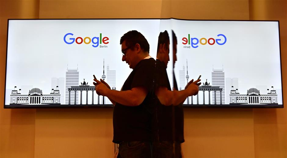 A man stands in front of a screen picturing Berlin landmarks during the opening day of a new Berlin office of US internet search giant Google in Berlin on January 22, 2019. (Photo by Tobias SCHWARZ / AFP)