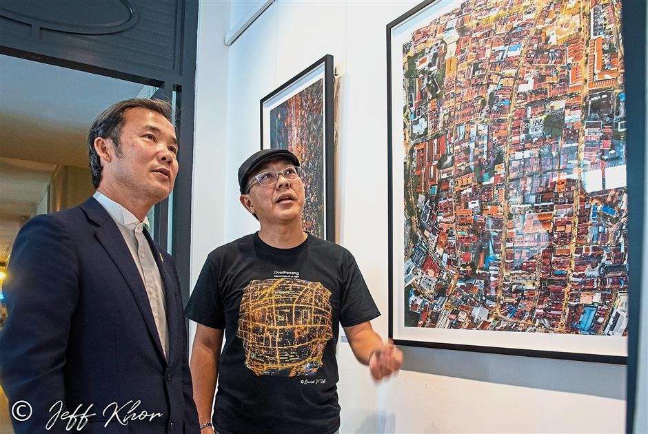 Loh (right) briefing Yew on one of the exhibits of his 'Over Penang' showcase at the E&O Hotel.