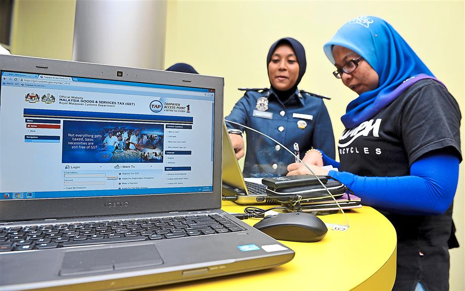 Getting help: Customs officer Nor Shamshida Md Isa assisting Noor Azaliah Jaafar (right) as she registers her company information on the Taxpayer Access Point (TAP) website at the GST Processing Centre ?in Kelana Jaya. — Bernamapic