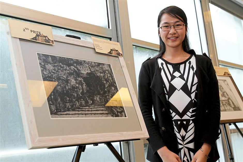 Chong Chin Kwan, 22, with her artwork 'Kek Lok Tong, Ipoh' which won second prize in the Chia Wai Kin from Dasein Academy of Art won second prize in the Watercolour category with 'Still'. Charcoal/Pencil/Ink category.