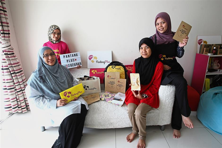 Pantang Plus founder and chief executive officer Zamzana Mohd Arifin with her staff and some of the merchandise they offer, at the company's HQ. - S.S.KANESAN/The Star