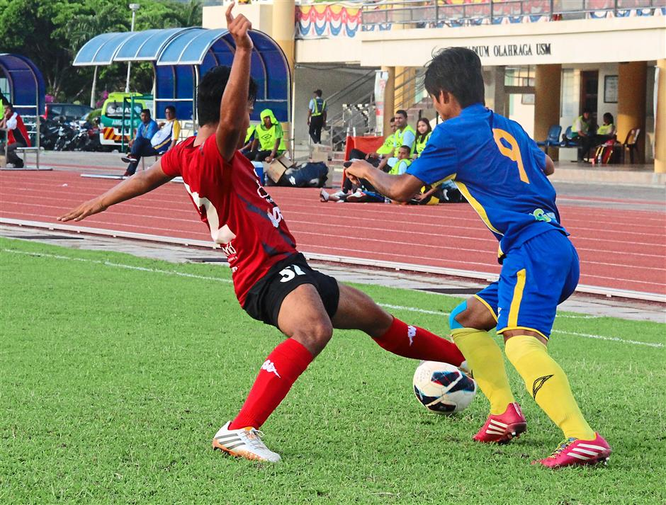 Blocking an opponent:   Kuala Lumpur defender Muhammad Azhim (in red) stretching forward in a bid to stop Penang striker Mohd Al-Hafiz Harun.