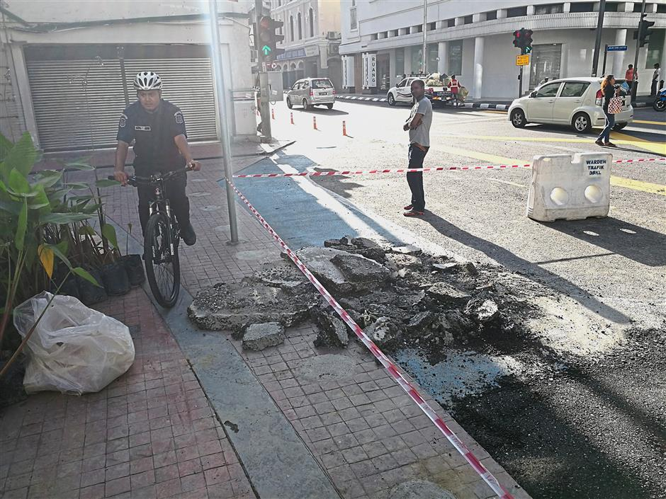 A cyclist avoiding construction debris dumped on the bicycle lane in Jalan Lebuh Pasar Besar.