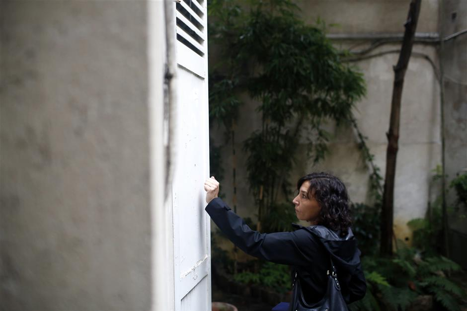 In this Friday, Sept. 21, 2018 photo, an inspector of Paris' town hall in charge of checking locations for tourists makes a door to door inspection, in Paris. The spectacular growth of Airbnb in Paris, the top worldwide location for the internet giant is also raising alarms in the French capital. Some Parisians and officials at City Hall blame the site for driving Parisian families out of the city center, leading to school closures and concerns that the French capital is losing its life and charms. (AP Photo/Thibault Camus)