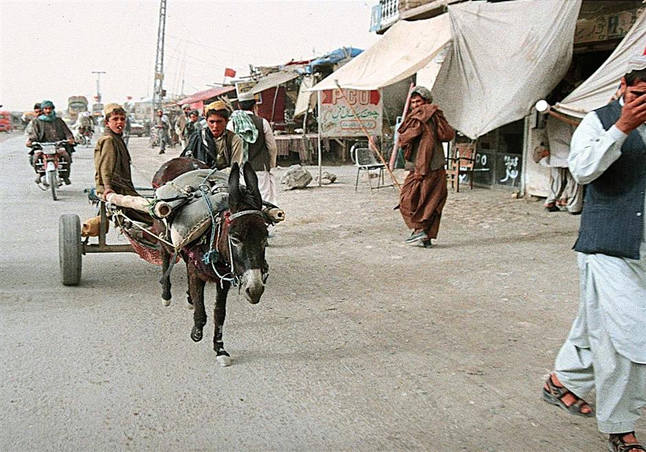 CHILDREN DRIVING DONKEY CARTS IN AFGHANISTAN. WITH LITERACY AT 31%, MOST CHILDREN DO NOT HAVE THE CHANCE TO GO TO SCHOOL BUT HAVE TO HELP THEIR FAMILIES EARN AN INCOME.