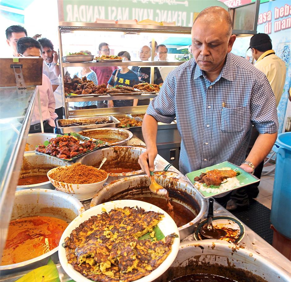 Dishes galore: Burhan of Original Penang Kayu Nasi Kandar says they use only quality spices to make their curries.