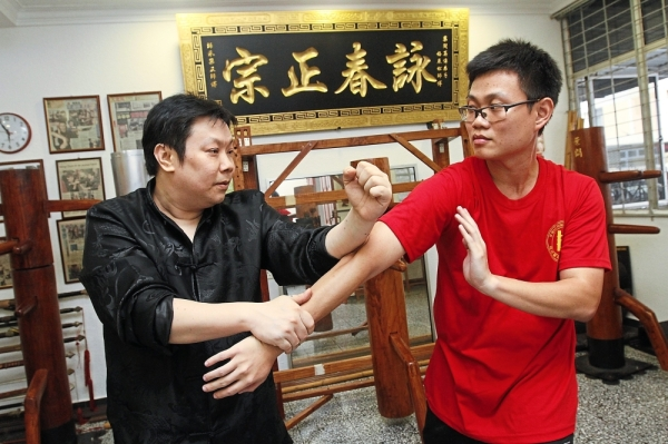 (From left) Boey teaching student Jack Tang, 31, at the centre.