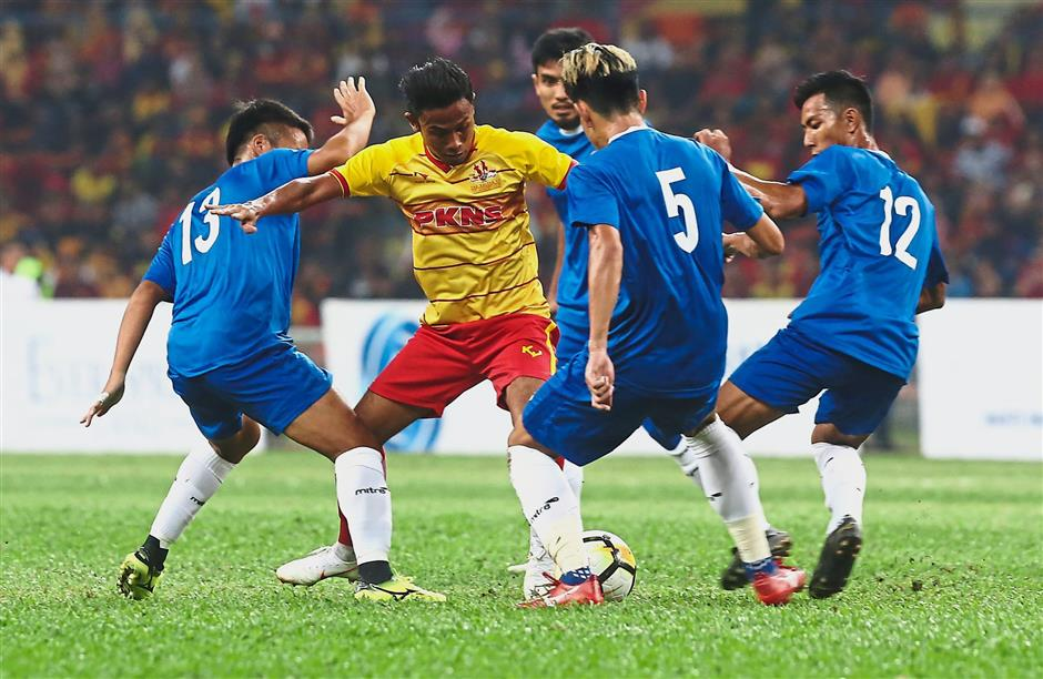 Selangor Selection's Mohd Khyril Muhymeen (in yellow jersey) finds himself surrounded by four Singapore players during their encounter.