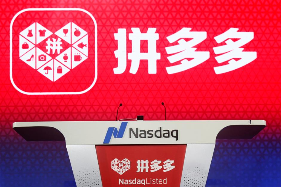The logo of online group discounter Pinduoduo is seen on a stage before the company\'s stock trading debut at the Nasdaq Stock Market in New York, during an event in Shanghai, China July 26, 2018. Picture taken July 26, 2018.  REUTERS/Stringer ATTENTION EDITORS - THIS IMAGE WAS PROVIDED BY A THIRD PARTY. CHINA OUT.