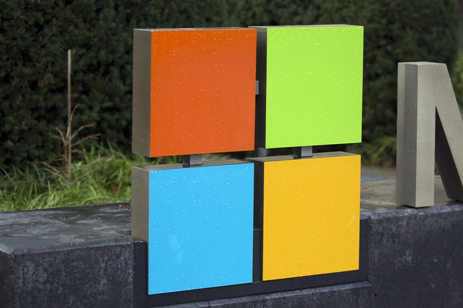 The Microsoft Corp. logo is displayed outside the company's main campus in Redmond, Washington, U.S., on Tuesday, Dec. 19, 2017. In the race to commercialize a new type of powerful computer, Microsoft has just pulled up to the starting line with a slick-looking set of wheels. The Redmond, Washington-based tech giant is competing with Alphabet Inc.'s Google, International Business Machines Corp. and a clutch of small, specialized companies to develop quantum computers u2013 machines that, in theory, will be many times more powerful than existing computers by bending the laws of physics. Photographer: David Ryder/Bloomberg