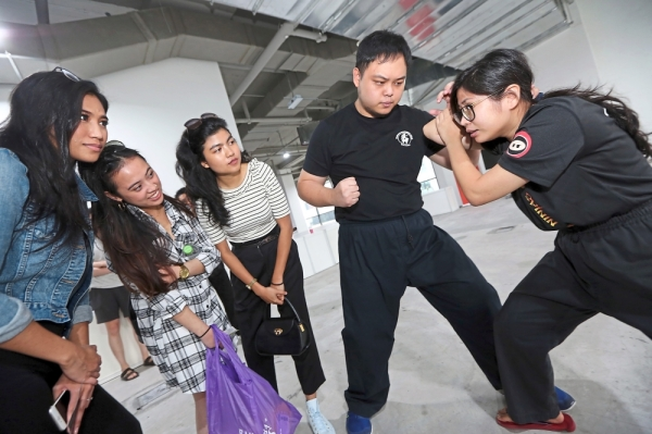 (From left) Aimanissa, Nazierah and Aliah watching the demonstration by trainers Quek Chun Leng and Carol Wong Xin Yi during the self-defence for women and children session at the fiesta.