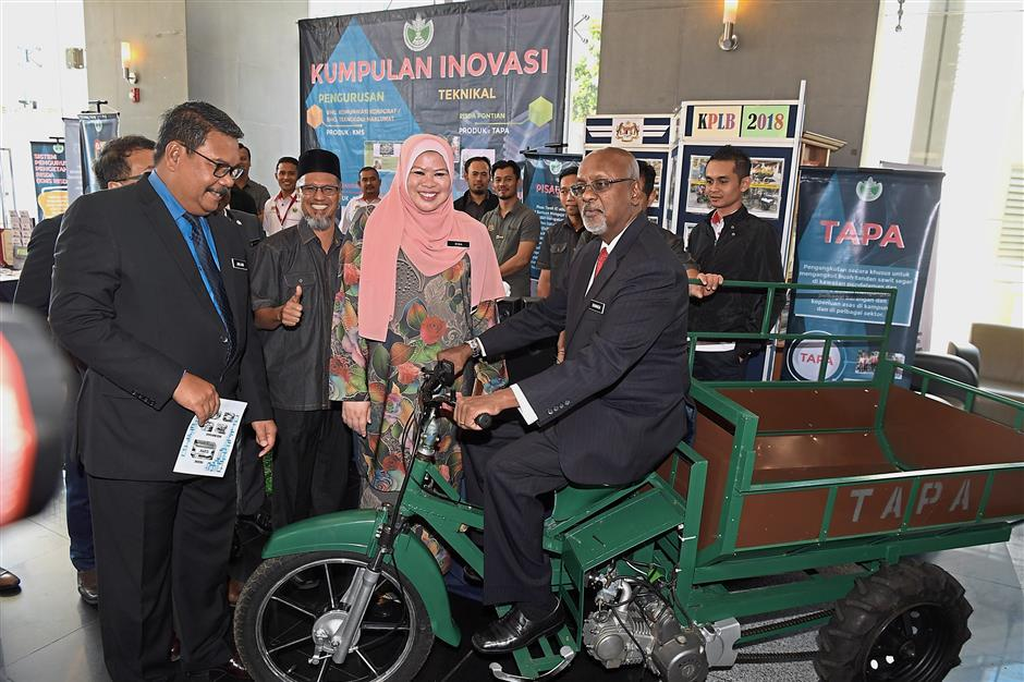 Deputy minister: Checking out a motorcycle adapted to carry oil palm fruit bunches with his minister, Datuk Seri Rina Mohd Harun, earlier this month. Also present is the Rural and Regional Development Ministry's Chief Secretary Datuk Dr Ahmad Jailani Muhamed Yunus (left).