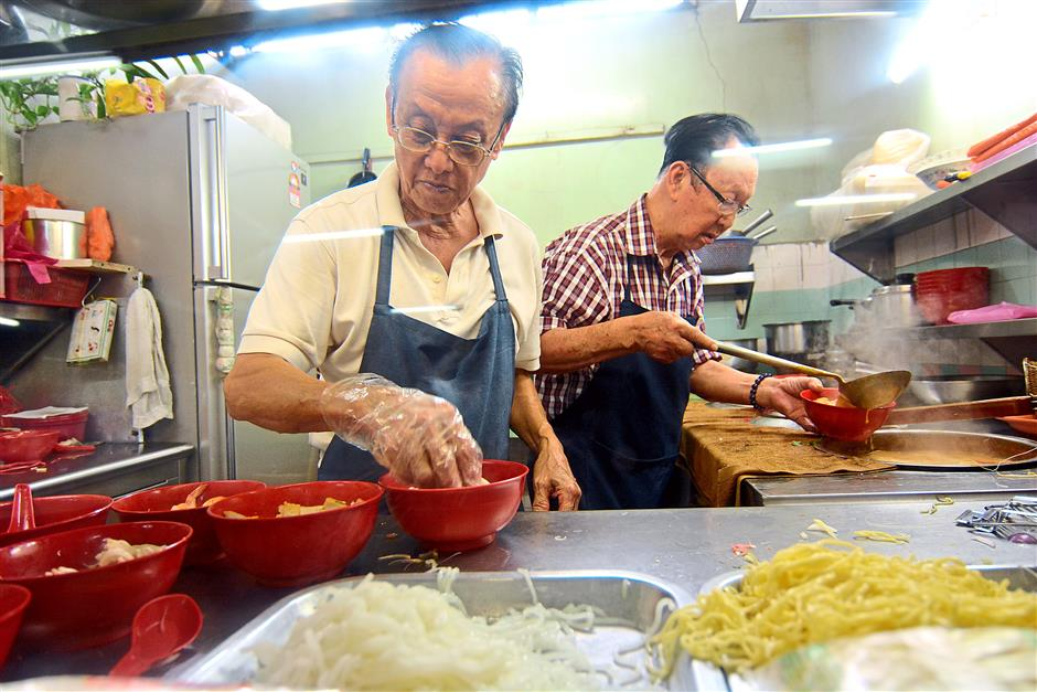 Working together: For their curry laksa, the brothers Seng Hin (left) and Wai Lum add beancurd puff, beansprouts, short green beans, fish cakes, chicken pieces, prawns and cockles. Extra ingredients like boiled eggs can be added with additional charges.