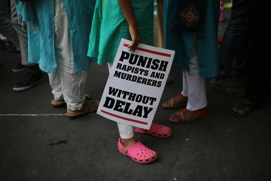 FILE - In this April 15, 2018 file photo, an Indian protestor stands with a placard during a protest against two recently reported rape cases as they gather near the Indian parliament in New Delhi, India. Violent crime against women has been on the rise in India despite tough laws that were enacted five years ago. Responding to widespread outrage over the recent rape and killings of young girls and other attacks on children, India's government in April approved the death penalty for people convicted of raping children under age 12. (AP Photo/Oinam Anand, File)