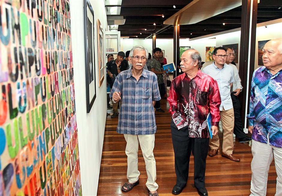 1 Daim (left) at the launch of the Open Exihibition 2015 at the Shah Alam Gallery. With him are Prof Raja Zahabuddin (in red shirt) and Mohd Said (right). 2 Visitors to the gallery looking at an acrylic painting by Mohamad Hassan titled 'Hadrah: Alunan Dari Bendang'. — Photos: ROHAIZAT MD DARUS/The Star