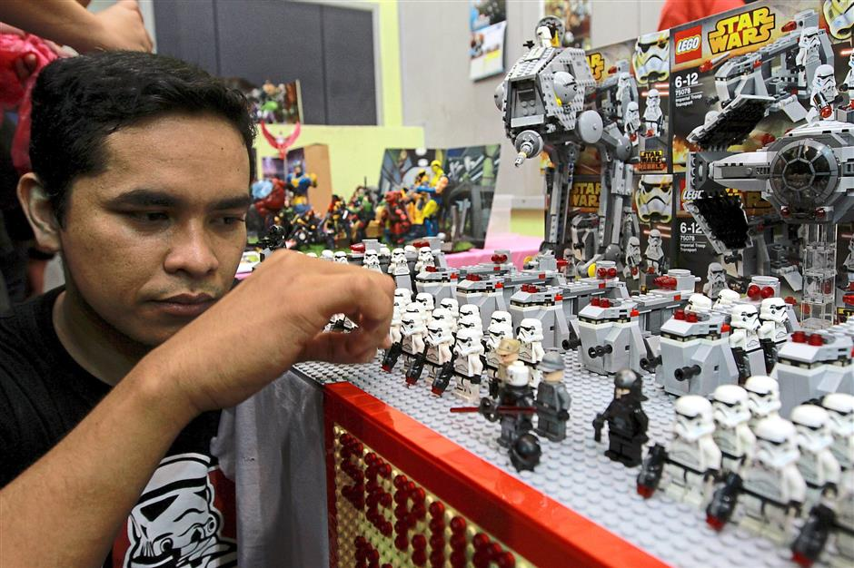 Set up: Mohd Faizol Ismail, 32, manning his club's booth which had Lego Star Wars characters.