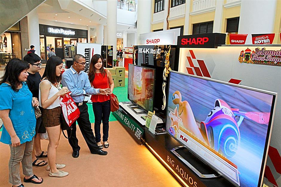 Choices aplenty: Burhanuddin (in blue shirt) briefing customers on the 80-inch Sharp Big AQUOS Quattron Pro LCD TV.