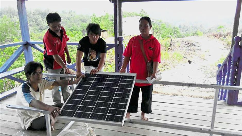 Productive project: A solar panel ready fo use in Sabah, thanks to Swepau2019s Barefoot solar project. (Inset) Tambakauu2019s humble background drove her to help others.