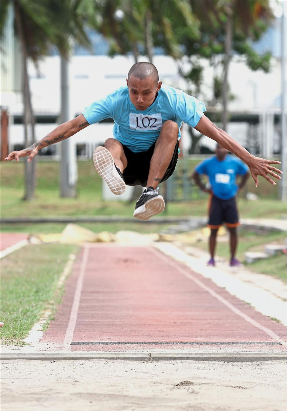 A participant soars as he attempts the long jump.