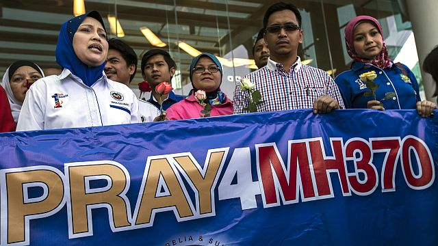 Group of persons holding roses and a banner as they pray for missing flight MH370 at a hotel in Putrajaya, Malaysia, 10 March 2014. - EPA