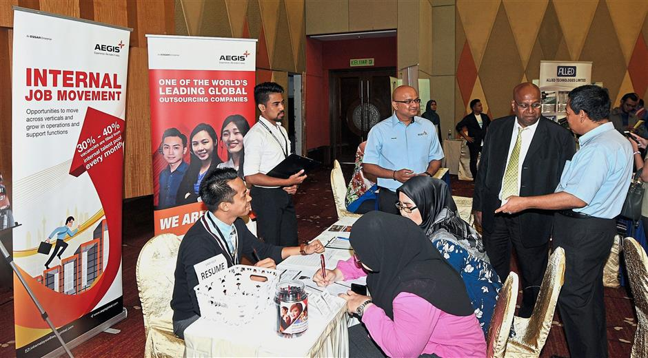 Ramakrishnan (second from right) and Ismail (right) visiting booths after launching Iskandar Malaysia Employment Fair 2018.