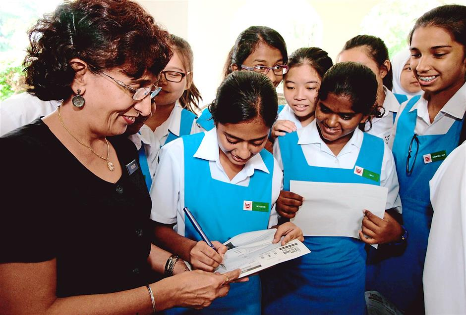 Count us in: Mungit (left) helping her students fill the entry forms.