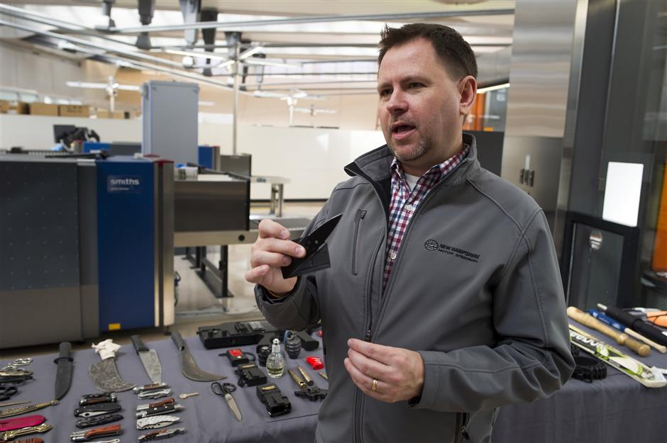 David Johnston, TSA's social media director, displays a knife which was confiscated from a passenger, at Dulles International Airport in Dulles, Va., Tuesday, March 26, 2019. TSA's social media presence has been something of a model for other federal agencies _ striking a tone is humorous, but still gives travelers informational dos and don'ts. (AP Photo/Cliff Owen)