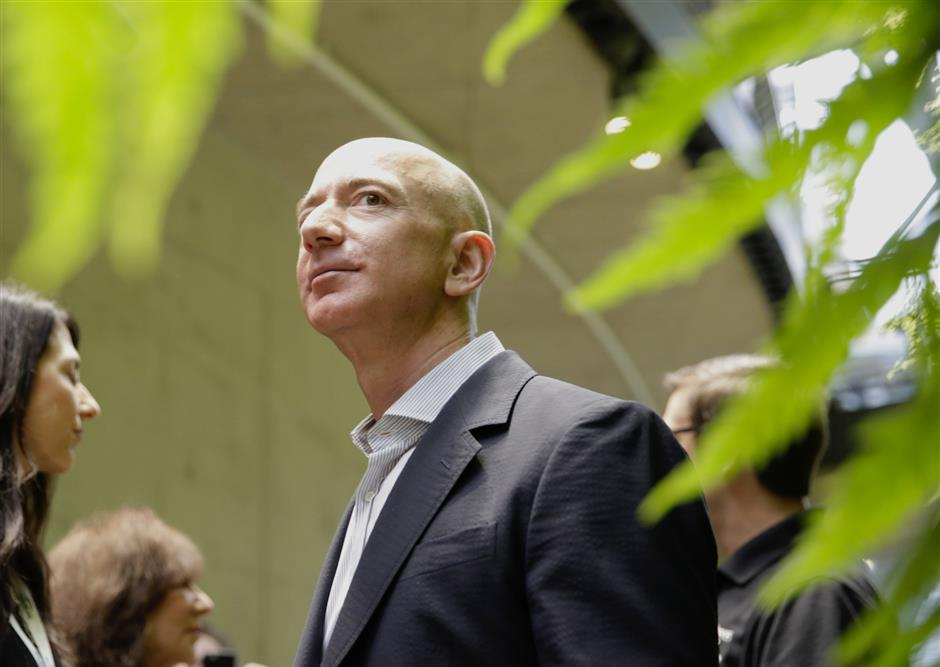 (FILES) In this file photo taken on January 29, 2018 Chief Executive Officer of Amazon, Jeff Bezos, tours the facility at the grand opening of the Amazon Spheres, in Seattle, Washington.u00a0 Jeff Bezos is officially the richest person on the planet thanks to the success of Amazon -- but his bold vision extends to space and even time itself.With Amazon's share price up nearly 60 percent during the past year, the personal wealth of the company's 54-year-old founder has doubled to more than $110 billion. / AFP PHOTO / JASON REDMOND