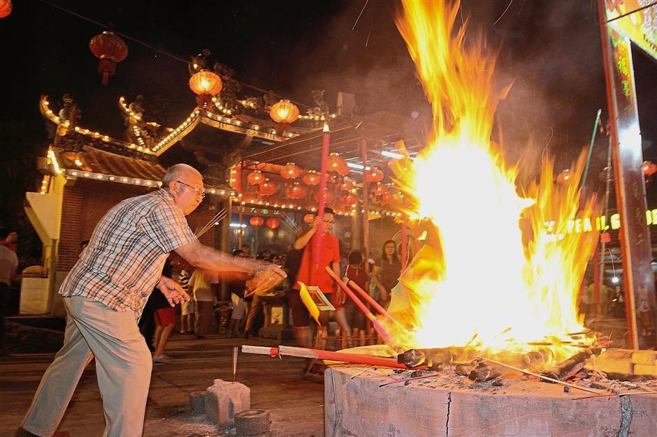 An elderly devotee burning prayer paraphernalia at the temple compound.